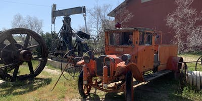An old truck and some historic oil equipment.